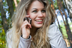 Die junge Frau mit Telefon im Park Stockfoto