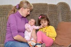 Die junge Frau mit zwei kleinen Kindern sitzen auf einem Sofa Lizenzfreie Stockfotos