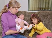 Die junge Frau mit zwei kleinen Kindern sitzt auf einem Sofa Lizenzfreies Stockfoto
