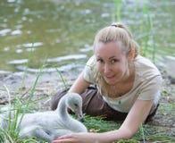 Die junge Frau nahe einem Vogelbaby eines Schwans auf der Bank des Sees Lizenzfreie Stockbilder