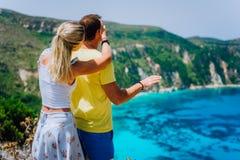 Die junge Frau Petani-Standpunkts, die ihren Freund schließt, mustert vor herrlichem Meerblickpanorama Türkis Petani-Strand stockfotografie