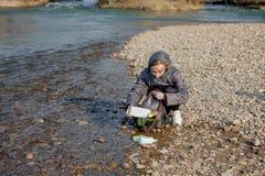 Die junge Frau, die Plastikabfall vom Strand sammelt und ihn in schwarze Plastiktaschen f?r setzt, bereiten auf S?ubern und Wiede lizenzfreie stockfotografie