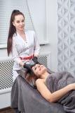 Die junge Frau, die Schönheitsverfahren im Salon durchmacht und genießt stockfotografie