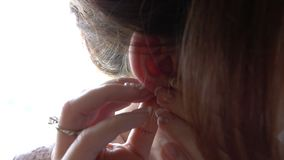 Die junge Frau setzt an schöne Ohrringe - Zeitlupe stock video
