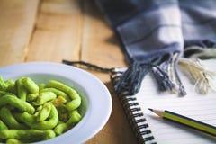 Die junge Frau, die Snäcke isst, schreiben einen Geschichtenbrief über jemand lizenzfreies stockbild