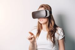 Die junge Frau, die Spiel in den Gläsern der virtuellen Realität spielt, benutzen digitalen Touch Screen der Tablettensteuervirtu lizenzfreie stockbilder