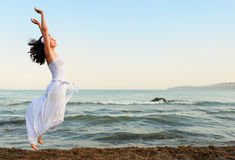 Die junge Frau springt auf Seeküste Lizenzfreie Stockfotografie