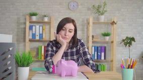 Die junge Frau, die am Tisch, verwirrt sitzt, betrachtet das Sparschwein stock video