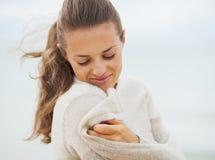 Die junge Frau träumend, die in der Strickjacke auf kalt einwickelt, setzen Sie auf den Strand Stockbilder