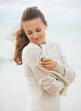 Die junge Frau träumend, die in der Strickjacke auf kalt einwickelt, setzen Sie auf den Strand lizenzfreies stockfoto
