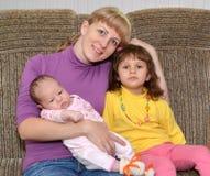 Die junge Frau umfasst die dreijährige Tochter und das Baby Lizenzfreies Stockbild