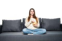 Die junge Frau verbringt seine Freizeit zu Hause fernsehend auf der Couch und kaut Chips Lizenzfreies Stockbild