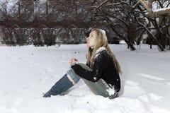 Die junge gefrorene Frau unter dem fallenden Schnee Stockfotos