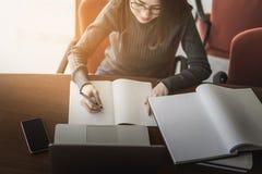Die junge Geschäftsfrau, die bei Tisch sitzt und Kenntnisse im Notizbuch, auf Tabelle nimmt, ist Laptop, Smartphone und Tasse Kaf stockfotografie