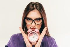 Die junge Geschäftsfrau in den Gläsern mit Wecker stockbilder
