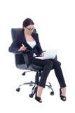 Die junge Geschäftsfrau, die auf Stuhl sitzt und mit Laptop arbeitet, ist Stockfoto