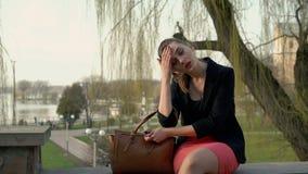 Die junge Geschäftsfrau, die aus ein Bürogebäude herauskommt und sitzt auf der Treppe stock footage