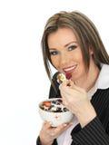 Die junge Geschäftsfrau, die eine Schüssel Getreide mit Jogurt isst und ist Lizenzfreie Stockfotos