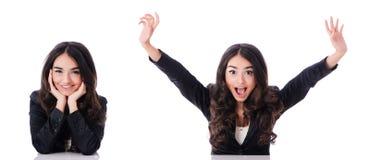 Die junge Geschäftsfrau, die am Schreibtisch auf Weiß sitzt Stockbild