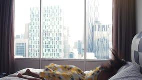 Die junge glückliche Brunettefrau, die unten auf Bett fällt, haben Spaß zur unvorsichtigen Wochenendenzeit Langsame Bewegung 3840 stock video