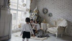 Die junge glückliche Familie umarmt nahe mit dem Weihnachtsbaum Glückliches Weihnachten und guten Rutsch ins Neue Jahr stock video