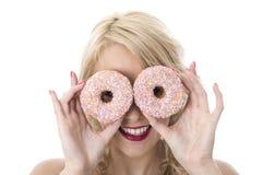 Die junge glückliche Frau, die mit zwei spielt, gefror Schaumgummiringe über Augen Stockfoto
