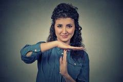 Die junge, glückliche, lächelnde Frau, die Zeit heraus zeigt, gestikulieren mit den Händen Stockbild