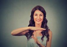Die junge, glückliche, lächelnde Frau, die Zeit heraus zeigt, gestikulieren mit den Händen Stockfotos