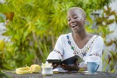 Die junge glückliche und attraktive schwarze afroe-amerikanisch Hippie-Frau, die mit digitaler Tablette draußen am Café arbeitet, Lizenzfreie Stockbilder