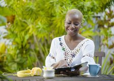 Die junge glückliche und attraktive schwarze afroe-amerikanisch Hippie-Frau, die mit digitaler Tablette draußen am Café arbeitet, Stockfotografie