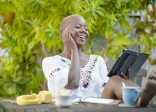 Die junge glückliche und attraktive schwarze afroe-amerikanisch Hippie-Frau, die mit digitaler Tablette draußen am Café arbeitet, Stockfotos