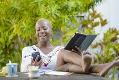 Die junge glückliche und attraktive schwarze afroe-amerikanisch Hippie-Frau, die mit digitaler Tablette draußen am Café arbeitet, Stockbild