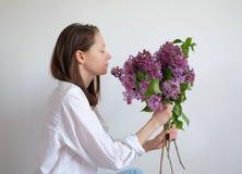 Die junge hübsche Frau, die Geruch der Blumenstraußflieder genießt, blüht geschlossene Augen über weißem Hintergrund lizenzfreie stockbilder