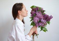 Die junge hübsche Frau, die Geruch der Blumenstraußflieder genießt, blüht geschlossene Augen über weißem Hintergrund stockbild