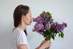 Die junge hübsche Frau, die Geruch der Blumenstraußflieder genießt, blüht geschlossene Augen über weißem Hintergrund stockbilder