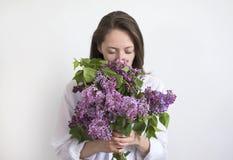 Die junge hübsche Frau, die Geruch der Blumenstraußflieder genießt, blüht geschlossene Augen über weißem Hintergrund Lizenzfreie Stockfotos