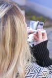 Die junge kaukasische blonde Frau, die Lippen anwendet, bilden in Bewegung Lizenzfreie Stockbilder