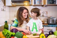 Die junge Kochmutter, die mit ihrem kleinen Sohn im kitche steht lizenzfreies stockfoto