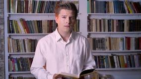 Die Junge, die konzentriert werden, bemannen sind Lesebuch in der Bibliothek und passen an der Kamera auf stock footage