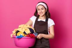 Die junge lächelnde nette Frau, die mit rosa Becken, viel Wäscherei, es mit beiden Händen halten habend geht, schaut positiv u lizenzfreie stockfotografie