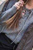 Die junge moderne Frau, die eine Bomberjacke tragen und ein übergroßes Graues schnüren sich oben Strickjacke Stockbild