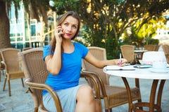 Die junge moderne Geschäftsfrau, die am Telefon spricht und macht Anmerkungen Lizenzfreie Stockfotografie