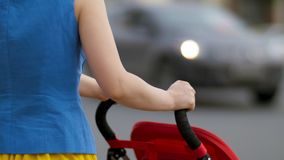 Die junge Mutter, die mit Kinderwagen an der Straße zurück geht, sehen nah oben an Mutter mit einem Spaziergänger geht hinunter d Lizenzfreie Stockbilder