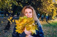 Die junge nette nette Mädchenfrau, die mit gefallenem Herbstgelb spielt, verlässt im Park nahe dem Baum und lacht und lächelt Stockbilder