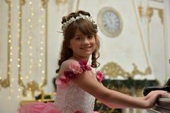 Die junge Prinzessin im Weiß mit einem Klavier Stockbilder