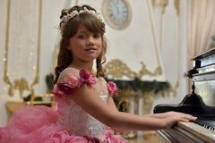Die junge Prinzessin im Weiß mit einem Klavier Lizenzfreies Stockfoto