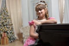 Die junge Prinzessin im Weiß mit einem Klavier Stockfotografie