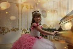 Die junge Prinzessin im Weiß mit einem Klavier Lizenzfreie Stockfotos