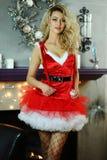 Die junge schöne blonde Frau, die als sexy Sankt-Helfer in der roten Kleider- und Fischnetzstrumpfware aufwirft im Weihnachten ge Lizenzfreie Stockfotos