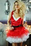 Die junge schöne blonde Frau, die als sexy Sankt-Helfer in der roten Kleider- und Fischnetzstrumpfware aufwirft im Weihnachten ge Lizenzfreie Stockbilder